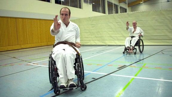 Zwei Männer in einer Sporthalle beim Rollstuhl-Karate.