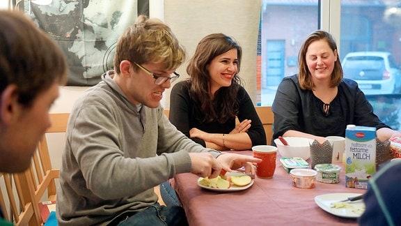 Menschen sitzen an einem Tisch beim Frühstück