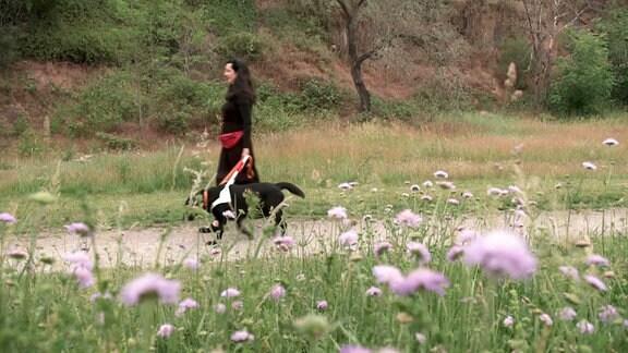 Eine Frau mit Hund beim Spaziergang.