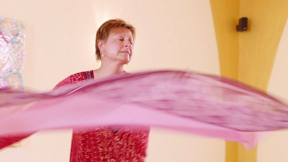 Eine Frau in der Drehung mit einem wehenden pinkfarbenen Tuch in der Hand. Sie hält die Augen geschlossen.