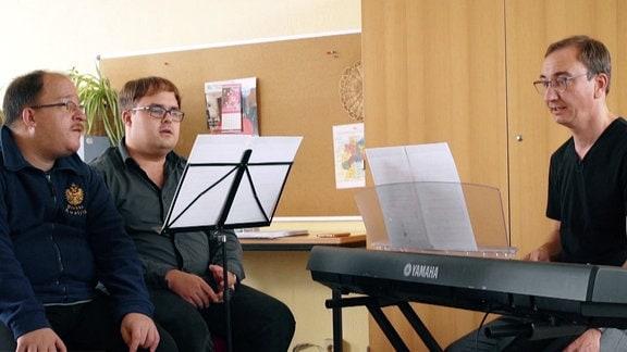 Drei Männer, Notenständer, Musikinstrument