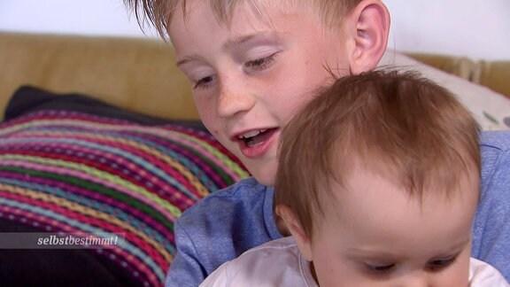 Ein Junge hält seinen kleine Schwester fest.