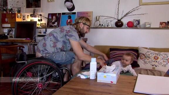 Ein Mann im Rollstuhl wickelt ein Kind.