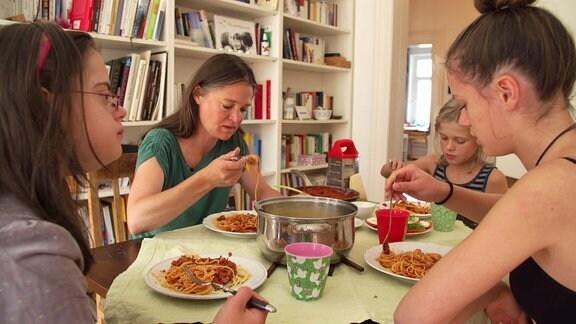 Eine Frau und drei Mädchen sitzen an einem Tisch und essen.