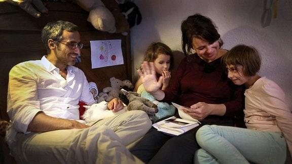 Familie sitzt auf einem Bett.