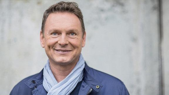 Moderator Axel Bulthaupt vor einer Mauer.
