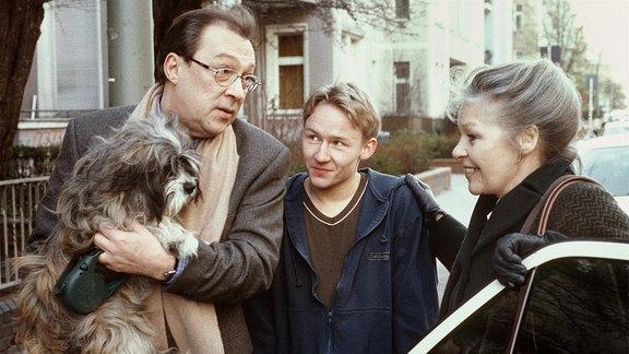 Hauptkommissar Schmücke hält einen Hund auf dem Arm und unterhält sich mit seiner Freundin Edith Reger (Marita Böhme) und Bastian, einen wichtigen Zeugen.