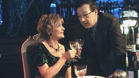 Hauptkommissar Herbert Schmücke (Jaecki Schwarz) stößt mit seiner alten Schulfreundin Ulrike Bix (Gila von Weitershausen) beim Abendessen an.