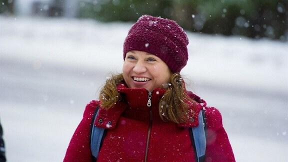 Disa (Maria Sid) strahlt, sie trägt eine Mütze und eine Winterjacke, es schneit und im Hintergrund ist schon eine Schicht von Schnee zu sehen.