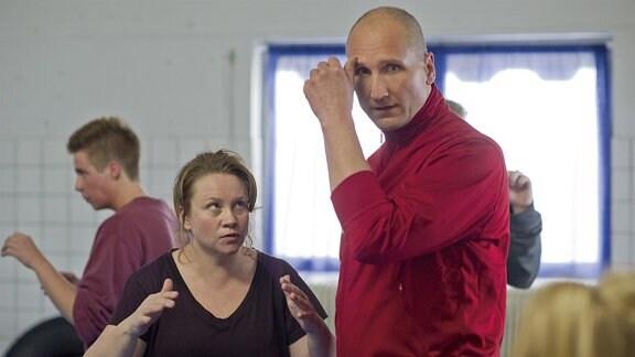 Ihr Krav-Maga-Trainer (Fredrik Hammar) steht neben Disa (Maria Sid) und kratzt sich am Kopf, sie sieht ihn in Kampfstellung konzentriert an.
