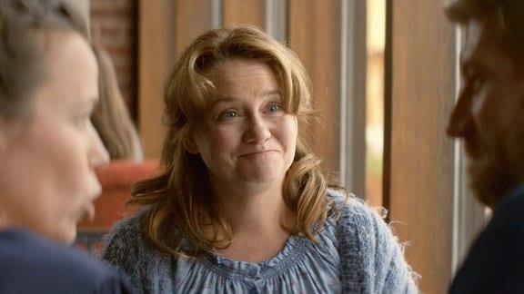Disa (Maria Sid, M.) sitzt mit enttäuschtem und überraschtem Gesicht einem Paar gegenüber.