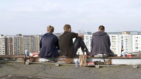 Jojo (Kay Liemann), Fuchser (Adrian Spielbauer), Balla (Luis Quintana) sitzen nebeneinander am Rand des Dachs eines Plattensbaus in Rostock