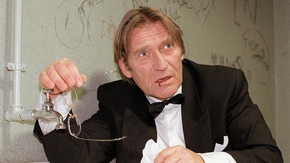 Johannes Breutigam (Matthias Habich) mit einer aufgeschlagenen Lippe stützt sich an einem Waschbecken.