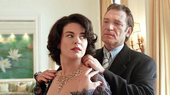 Johannes Breutigam (Matthias Habich) hängt Claudia Breutigam (Barbara Auer) eine Halskette um.