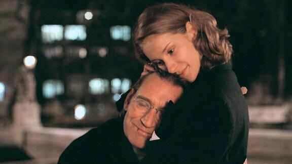Frankie (Chiara Schoras) hält den sich anschmiegenden Johannes Breutigam (Matthias Habich) lächelnd in ihren Armen.