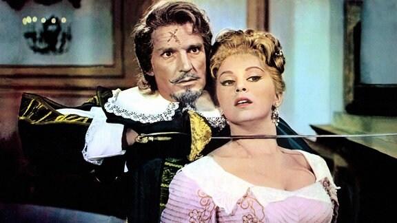Der Herzog von Montserant (Georges Marchal) hält seiner Nichte Diana (Alessandra Panaro) von hinten den Degen an den Hals.
