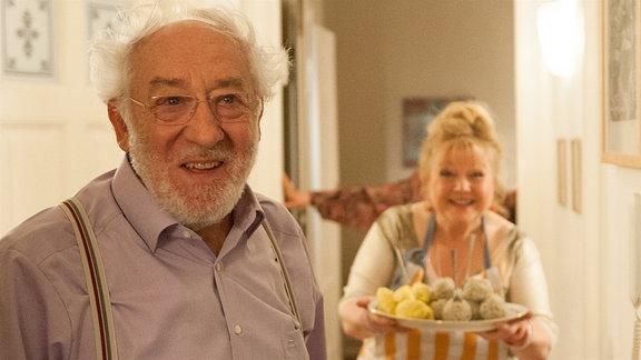 Edek Rotwachs (Dieter Hallervorden) steht in seiner Wohnung und lächelt nach vorn, während im Hintergrund seine Mitbewohnerin Zofia (Franziska Troegner) eine Schüssel mit Fleischklopsen hält.