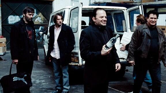 Mehrere Männer stehen vor einem Transporter. Ein Mann hält eine Flasche Schnaps in der Hand.