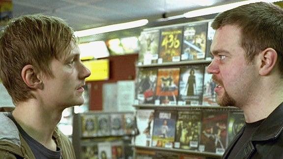Zwei Männer unterhalten sich in einer Videothek.