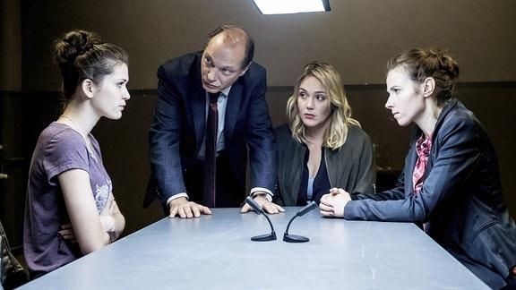 Emilia (li, Caroline Hartig) wird von Kommissariatsleiter Peter Michael Schnabel (mi.li, Martin Brambach) und den Ermittlerinnen Heni Sieland (mi.re, Alwara Höfels) und Karin Gorniak (re, Karin Hanczewski) befragt.