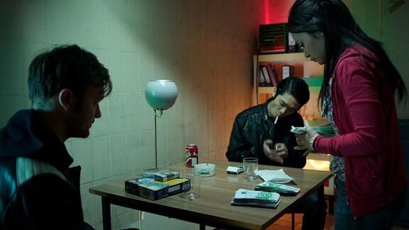 Tommy (Vincent Redetzki, li.) wickelt ein Geschäft bei Honza (Yung Ngo) und Hai Yen (Mai Duong Kieu) ab.