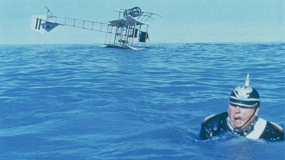 Oberst Manfred von Holstein (Gert Fröbe) in Uniform und schwimmend. Im Hintergrund treibt sein abgestürztes Flugzeug auf dem Wasser.