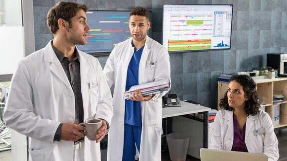 Dr. Sherbaz (Sanam Afrashteh, r.) ist erstaunt, als Dr. Niklas Ahrend (Roy Peter Link, l.) seinen Kollegen Dr. Moreau (Mike Adler, M.) um Hilfe bittet.