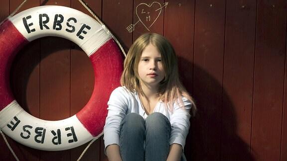 """Die 11-jährige Lola (Tabea Hanstein) sitzt auf dem Hausboot, das den Namen """"Erbse"""" trägt."""