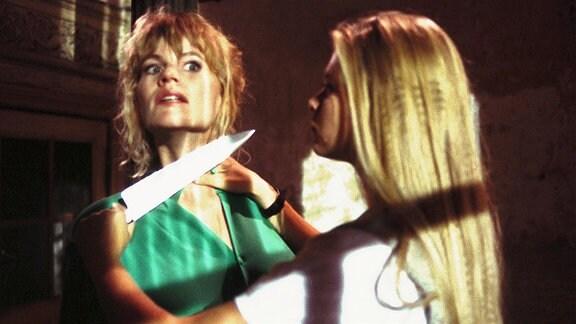 Barbara (Anne Kasprik, li.) wird von Melanie (Anne-Sophie Briest) mit einem Messer bedroht.