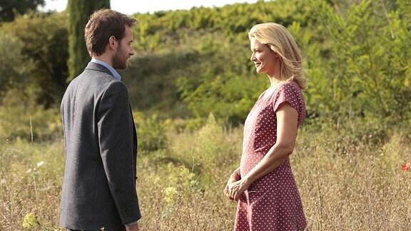 Ein Mann und eine Frau blicken sich inmitten einer Wiese an.