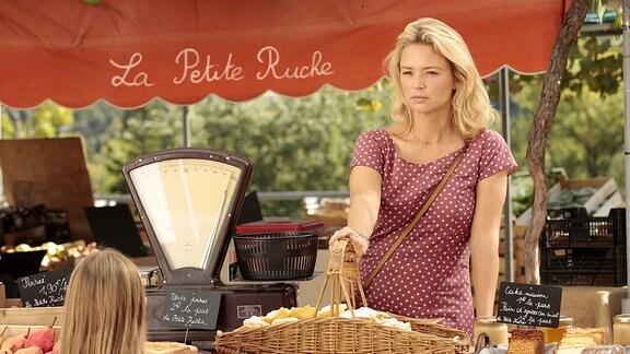 Eine Verkäuferin steht hinter einem Landhaus-Marktstand im Grünen.