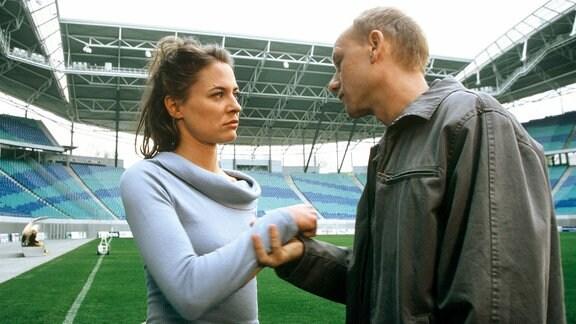 Anna Fellner (Julia Thurnau) will nicht auf alle Fragen von Kain (Bernd Michael Lade) im Leipziger Stadion antworten und versucht sich ihm zu entziehen.