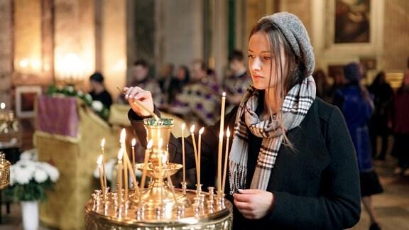 Maria Luise von Preußen zündet eine Kerze in der Kirche an.
