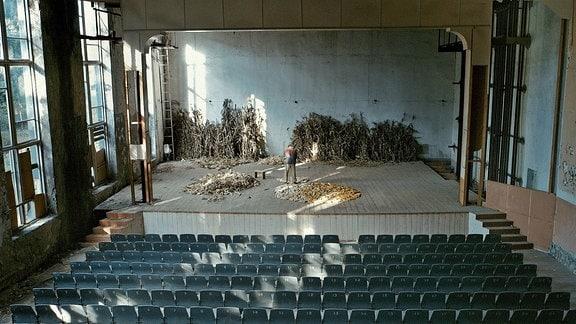 Auf einer Bühne werden Maiskolben verarbeitet.