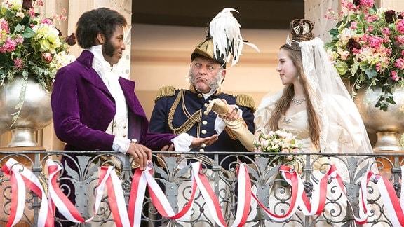 Das Brautpaar tritt vor das Schloss. Amélie (Leonie Brill) ist Königin, König Cristof (Leonard Lansink, mi.) übergibt seine Tochter an seinen Schwiegersohn Prinz Thabo (Elvis Clausen)
