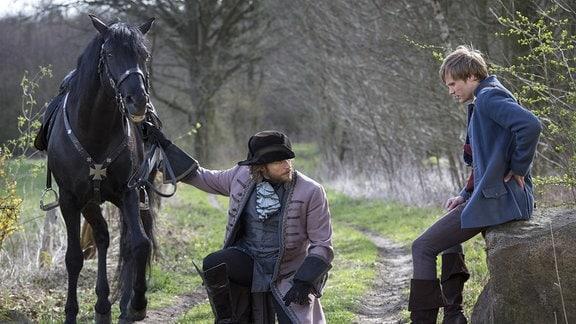 Ein Junker (Sebastian Ströbel) begutachtet den riesigen Goldklumpen, den Hans (Anton Spieker) mit sich trägt - und schlägt den ersten Tausch vor.