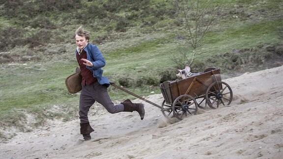 Hans (Anton Spieker) ist mit seinem getauschten Schwein im Bollerwagen im Glück.