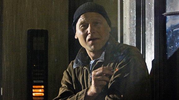 Frank Ziehrer (Bernd Michael Lade), der rauchend in einem Hauseingang steht, beobachtet den Anschlag auf Johannes Steuben.