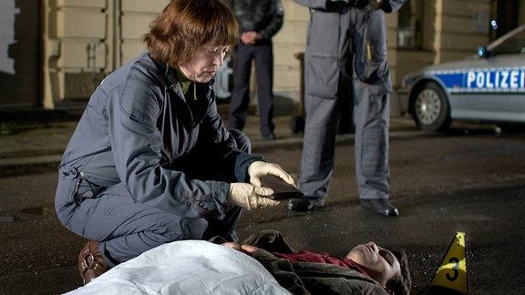 Das Opfer Johannes Steuben liegt auf der Straße und wird mit einem Tuch zugedeckt. Kriminaltechnikerin Weigand (Marie Gruber) sichert Spuren.