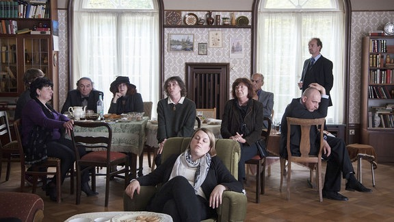 Die Trauergesellschaft (Sessel: Berit Künnecke als Dr. Anja; dahinter: Natascha Bondar als Mila; am Fenster: Jürgen Heimüller als Dr. Luchs)
