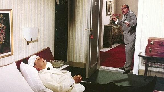 Ein Mann im Anzug liegt in einem Bett. Ein anderer Mann steht in der offenen Tür und erschrickt.