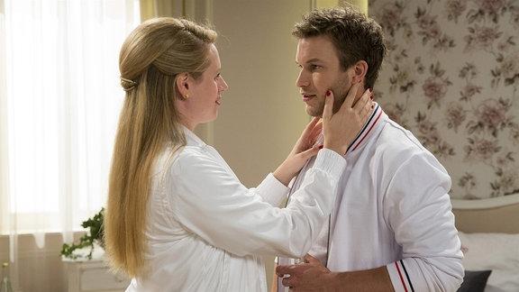 Ein Frau im weißen Kittel berührt einen Mann an Wange und Schulter.