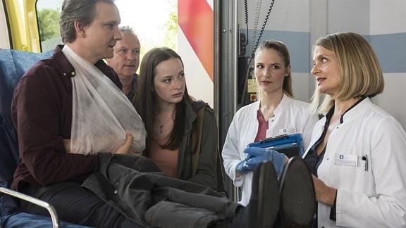 Olaf Schönholz (Sebastian Weber, l.) wird mit einem Schlüsselbeinbruch ins JTK eingeliefert. Seine Tochter Jeanette (Johanna Werner, 2.v.l.) ist den Ärzten gegenüber skeptisch. Julia Berger (Mirka Pigulla, 2.v.r.) und Dr. Franziska Ruhland (Gunda Ebert, r.) gehen von einem Routinefall aus.