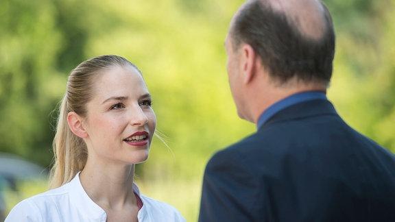 Julia (Mirka Pigulla, l.) hört amüsiert zu, als Berger (Horst Günter Marx, r.) ihr von seinem Ärger mit einer Sommelière erzählt. Zufällig lässt sich diese Weinkennerin gerade im JTK wegen ihres Geschmackverlustes behandeln.