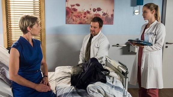 Dr. Marc Lindner (Christian Beermann, M.) und Julia Berger (Mirka Pigulla, r.) haben die Ursache für Denise' (Julia Grimpe, l.) Geschmacksverlust gefunden.