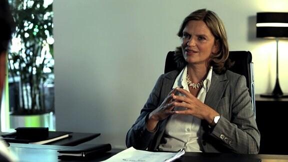 Produzentin (Kerstin Thielemann) an ihrem Schreibtisch