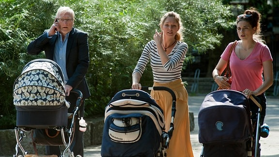 Anton (Ernst Stötzner), seine Tochter Marie (Leonie Parusel) und ihre Freundin Nele (Stephanie Krogmann) schieben die Kinderwagen.