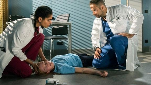 Tabea (Gina Alice Stiebitz, M.) hat absichtlich Tabletten gegen ihre Autoimmunkrankheit nicht genommen; als Vivi (Jane Chirwa, l.) und Matteo (Mike Adler, r.) sie finden, ist sie bereits bewusstlos.
