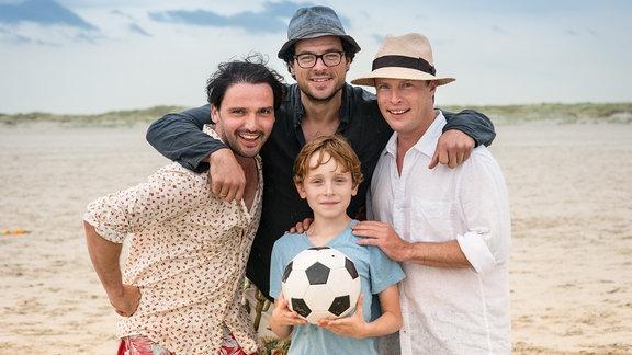 Drei Männer stehen um einen Jungen am Strand der einen Fußball hält. Die Stimmung ist locker gelöst.