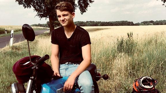 Ein junger Mann sitzt auf seinem Motorrad, an einem Feldrand geparkt.